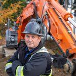 Worker in front of Hitachi Excavator